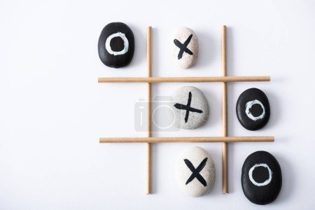 Photo pour Top view of tic tac toe game with grid made of paper tubes, and pebbles marked with crosses and naughts on white surface - image libre de droit