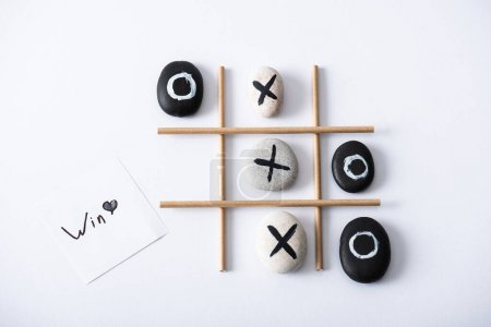Photo pour Top view of tic tac toe game with grid made of paper tubes, pebbles marked with crosses and naughts, and card with win inscription on white surface - image libre de droit
