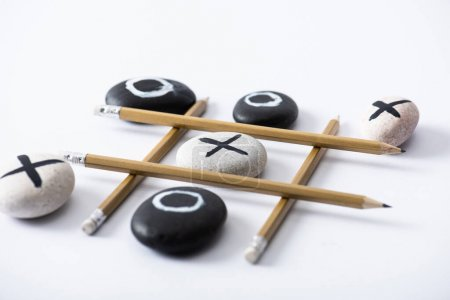 Photo for Tic tac toe game with grid made of pencils and pebbles marked with naughts and crosses on white surface - Royalty Free Image