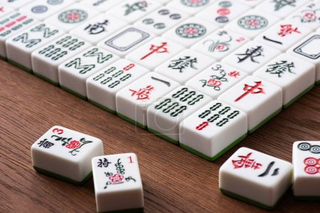 Photo pour KYIV, UKRAINE - 30 JANVIER 2019 : mise au point sélective du domaine des tuiles de jeu de mahjong avec signes et personnages sur table en bois - image libre de droit