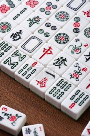 Photo pour KYIV, UKRAINE - 30 JANVIER 2019 : champ de tuiles de jeu de mahjong avec signes et personnages sur table en bois - image libre de droit