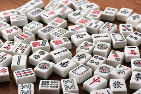 KYIV, UKRAINE - JANUARY 30, 2019: selective focus of white mahjong game tiles with signs and characters on wooden table