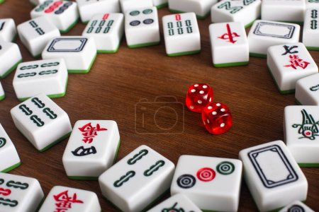 KYIV, UKRAINE - JANUARY 30, 2019: white mahjong game tiles and dice pair on wooden table