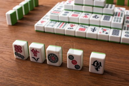 KYIV, UKRAINE - JANUARY 30, 2019: selective focus of rows and pyramid made of mahjong game tiles on wooden table