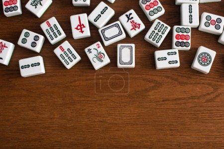 Photo pour KYIV, UKRAINE - 30 JANVIER 2019 : vue de dessus des tuiles blanches de jeu de mahjong avec des signes et des caractères sur la table en bois - image libre de droit