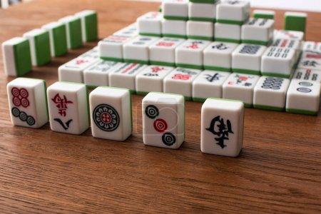 Photo pour KIEV, UKRAINE - 30 JANVIER 2019 : sélectif focus of rows and pyramid made of mahjong game tiles on wooden table - image libre de droit