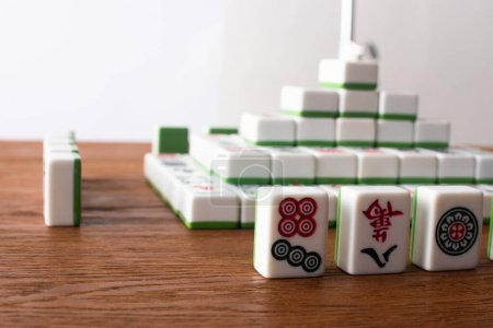 Photo pour KIEV, UKRAINE - 30 JANVIER 2019 : selective focus of rows and pyramid made of mahjong game tiles on wooden table isolated on white - image libre de droit