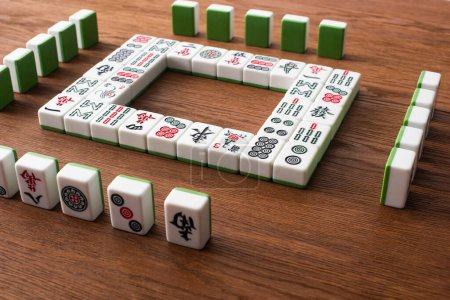 Photo for KYIV, UKRAINE - JANUARY 30, 2019: rows and square frame made of mahjong game tiles arranged wooden table - Royalty Free Image