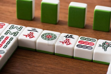 Photo for KYIV, UKRAINE - JANUARY 30, 2019: selective focus of mahjong game tiles rows on wooden table - Royalty Free Image