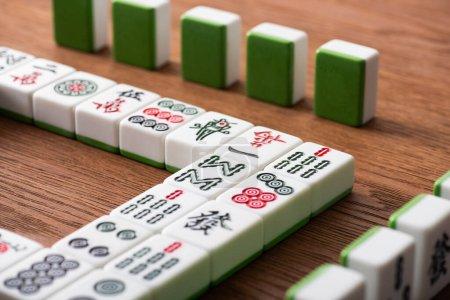 KYIV, UKRAINE - JANUARY 30, 2019: selective focus of mahjong game tiles rows on wooden table