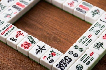 Photo pour KYIV, UKRAINE - 30 JANVIER 2019 : mise au point sélective du cadre carré et des rangées de tuiles de jeu de mahjong sur une table en bois - image libre de droit