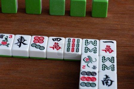 Photo pour KYIV, UKRAINE - 30 JANVIER 2019 : tuiles de jeu de mahjong avec signes et personnages sur table en bois - image libre de droit