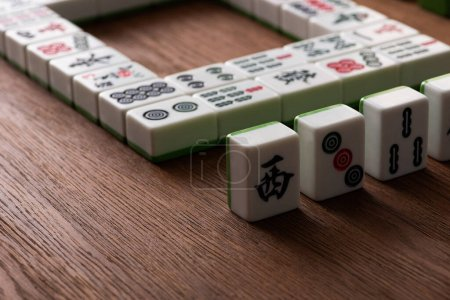 Photo for KYIV, UKRAINE - JANUARY 30, 2019: selective focus of mahjong game tiles with signs and characters on wooden table - Royalty Free Image