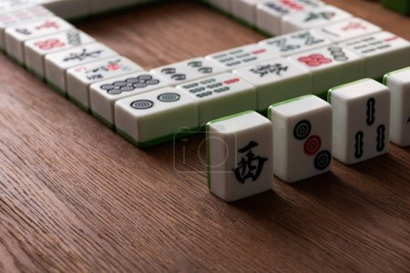 KYIV, UKRAINE - JANUARY 30, 2019: selective focus of mahjong game tiles with signs and characters on wooden table