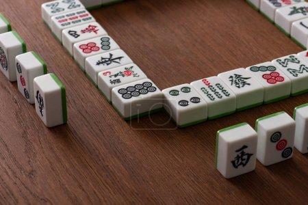 Photo for KYIV, UKRAINE - JANUARY 30, 2019: frame and rows of mahjong game tiles on wooden surface - Royalty Free Image