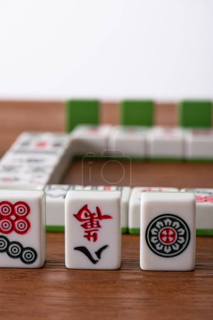 Photo for KYIV, UKRAINE - JANUARY 30, 2019: selective focus of mahjong game tiles with signs and characters on wooden surface isolated on white - Royalty Free Image
