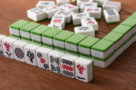 KYIV, UKRAINE - JANUARY 30, 2019: selective focus of mahjong game tiles with signs and symbols on wooden surface