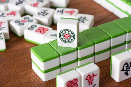 Photo pour KYIV, UKRAINE - 30 JANVIER 2019 : mise au point sélective des tuiles de jeu de mahjong avec signes et symboles sur la surface en bois - image libre de droit