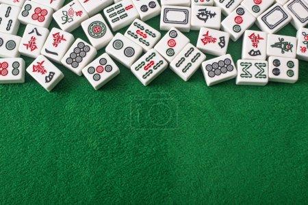 Photo pour KYIV, UKRAINE - 30 JANVIER 2019 : vue de dessus des tuiles blanches de jeu de mahjong avec des signes et des caractères sur la surface de velours vert - image libre de droit