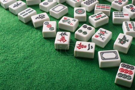 Photo pour KYIV, UKRAINE - 30 JANVIER 2019 : tuiles de jeu de mahjong avec signes et caractères sur la surface de velours vert - image libre de droit