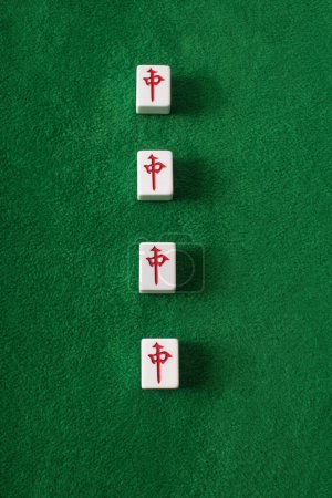 Photo for KYIV, UKRAINE - JANUARY 30, 2019: top view of mahjong game tiles row with characters on green velour surface - Royalty Free Image
