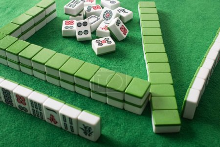 Photo for KYIV, UKRAINE - JANUARY 30, 2019: rows and stack of mahjong game tiles on green velour surface - Royalty Free Image