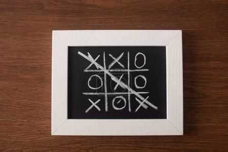 Foto de La vista superior del juego de dedos de tac en el tablero negro con la fila cruzada de cruces en la superficie de madera. - Imagen libre de derechos
