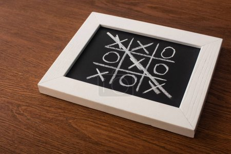 Photo for Tic tac toe game on blackboard with crossed out row of crosses on wooden surface - Royalty Free Image