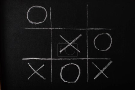 Photo for Top view of tic tac toe game on blackboard with chalk grid, naughts and crosses - Royalty Free Image