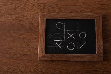 Photo pour Vue de dessus du jeu tic tac toe sur tableau noir avec grille de craie, nausées et croix sur surface en bois - image libre de droit