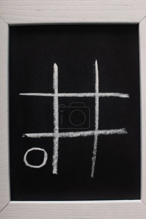 Photo for Top view of tic tac toe game on blackboard with chalk grid and naught on wooden surface - Royalty Free Image
