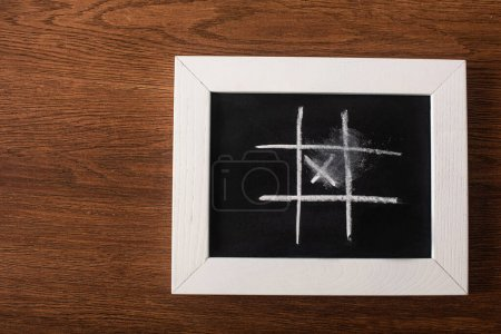 Photo for Top view of tic tac toe game on blackboard with chalk grid and cross on wooden surface - Royalty Free Image