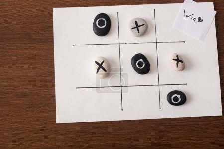 top view of tic tac toe game with stones marked with naughts and crosses, and card with win inscription on wooden surface