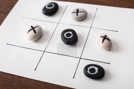 Photo for Tic tac toe game on white paper with pebbles marked with naughts and crosses on wooden surface - Royalty Free Image