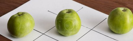 Photo for Panoramic shote of tic tac toe game on white paper with row of three green apples on wooden surface - Royalty Free Image