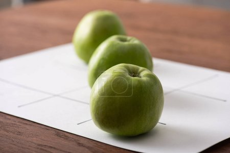 Photo for Selective focus of tic tac toe game with row of three green apples on white paper on wooden surface - Royalty Free Image