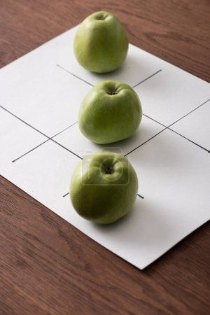 Photo for Tic tac toe game on white paper with row of three green apples on wooden surface - Royalty Free Image