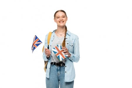 Photo pour Heureux joli étudiant avec sac à dos tenant livre et drapeau britannique isolé sur blanc - image libre de droit