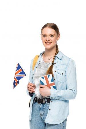 Photo pour Sourire joli étudiant avec sac à dos tenant livre et drapeau britannique isolé sur blanc - image libre de droit