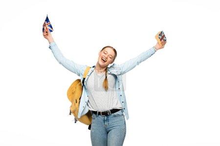 Photo pour Heureux élève avec livre à porter sur son sac à dos et drapeau britannique isolé sur blanc - image libre de droit