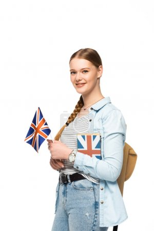 Photo pour Jolie élève souriante avec livre de sac à dos et drapeau britannique isolés sur blanc - image libre de droit
