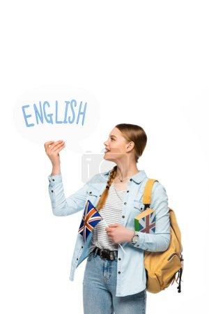 Photo for Smiling pretty student with backpack holding book, speech bubble with English lettering and British flag isolated on white - Royalty Free Image