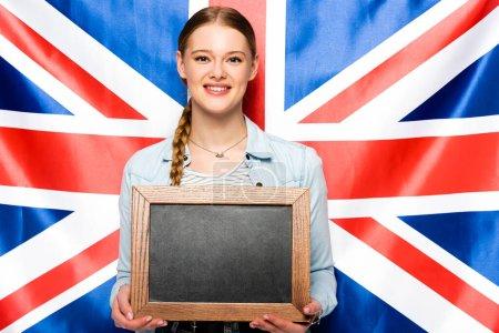 Photo pour Sourire jolie fille avec tresse tenant tableau blanc sur fond drapeau britannique - image libre de droit