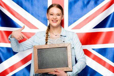 Photo pour Sourire jolie fille avec tresse pointant vers tableau blanc sur fond drapeau britannique - image libre de droit