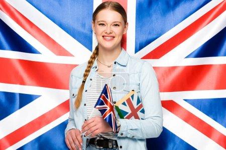 Photo pour Jolie fille souriante avec livre tenant une tresse sur fond de drapeau britannique - image libre de droit