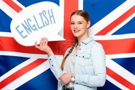 lächelndes hübsches Mädchen mit Zopf hält Sprechblase mit englischem Schriftzug auf britischem Flaggenhintergrund