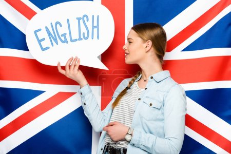 Photo for Smiling pretty girl with braid holding speech bubble with English lettering on uk flag background - Royalty Free Image