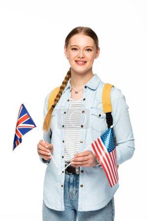 lächelndes Mädchen mit Zopf und Rucksack mit Fahnen Amerikas und des vereinigten Königreichs isoliert auf weiß