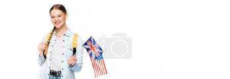 Photo pour Fille souriante avec tresse et sac à dos tenant des drapeaux d'Amérique et royaume uni isolé sur blanc, vue panoramique - image libre de droit