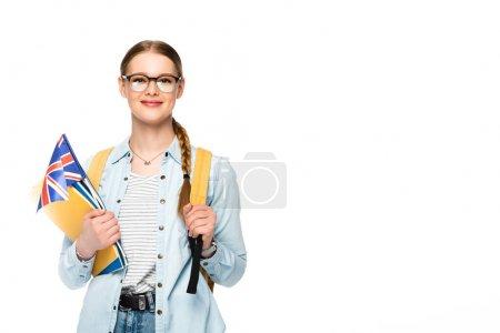 Photo pour Fille souriante dans des lunettes avec tresse et sac à dos tenant drapeau du royaume uni et copybooks isolés sur blanc - image libre de droit